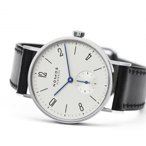 Mesure et art du temps - It embodies the NOMOS GLASHÜTTE watchmaking company like no other: the recognizable, classic and refined typography, a true gem of simplicity. The blued hands on a white silver metal dial, the numerous awards and its high precision, thanks to the hand-wound Alpha caliber from NOMOS. Horloger montre de luxe Bijoutier vannes