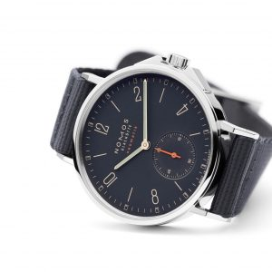 Mesure et art du temps - Almost black, but then again, not quite. This watch is the color of the ocean at night where it feels comfortable, even on a rough sea. The gold of the hands and the electric orange color of the seconds dial are colored lights. At its heart: the ultra-thin automatic caliber DUW 3001, firmly held to the caseback by six screws, a sapphire crystal and a crown guard.